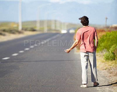 Buy stock photo A young man trying to hitch a ride while walking along a deserted road