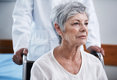 Buy stock photo Shot of an unhappy senior woman in a wheelchair being pushed by a doctor