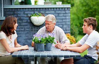 Buy stock photo Cropped shot of a senior couple sitting outside with their grandson