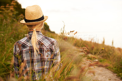Buy stock photo Rearview of a woman in a field wearing a straw fedora