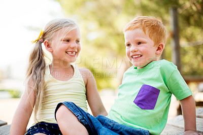 Buy stock photo Shot of a little brother and sister sitting outside