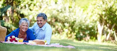 Buy stock photo Shot of a loving senior couple enjoying a picnic together outdoors