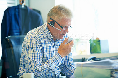 Buy stock photo Shot of a senior businessman wearing a headset using a dictaphone