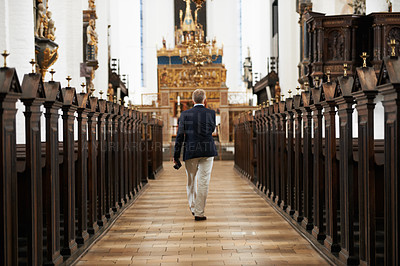 Buy stock photo Rearview shot of a senior man walking down the aisle of a church