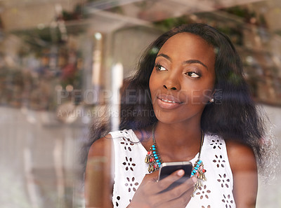 Buy stock photo Shot of an attractive young woman using a mobile phone in a cafe