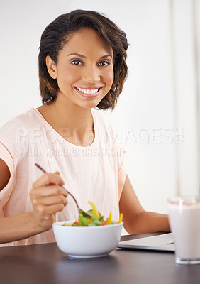Buy stock photo Portrait of a young woman enjoying a salad and working on a laptop at home