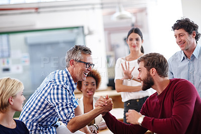 Buy stock photo Cropped shot of a group of designers looking excited during an informal office meeting