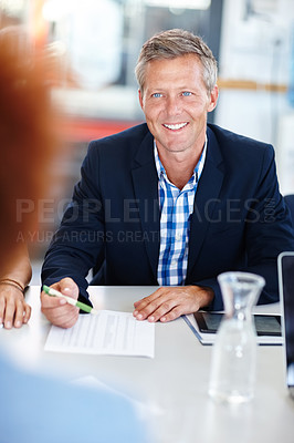 Buy stock photo A mature male manager sitting in a meeting with his team
