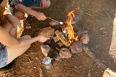 Buy stock photo Cropped shot of two campers roasting marshmallows over a campfire