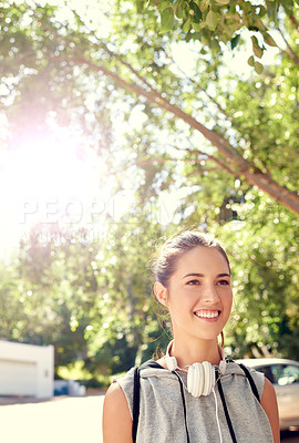 Buy stock photo Shot of a sporty young woman walking outside on a sunny day