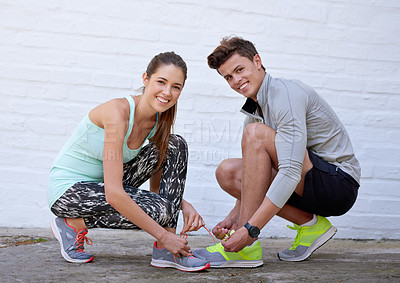 Buy stock photo Shot of a young couple tying their shoelaces before a workout