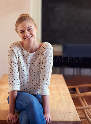 Buy stock photo Shot of a young woman sitting on the kitchen table