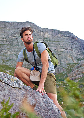 Buy stock photo Shot of a handsome young man scaling a mountain