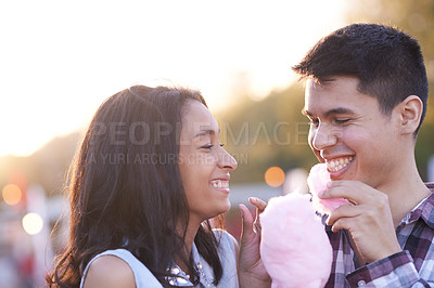 Buy stock photo Shot of a happy couple enjoying candy floss together at a fun fair