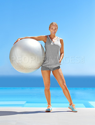 Buy stock photo Portrait of an attractive young woman holding an exercise ball by a swimming pool