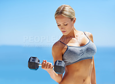 Buy stock photo Shot of a beautiful young woman lifting weights outside