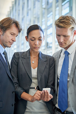 Buy stock photo Shot of businesspeople standing and looking at something on a mobile phone