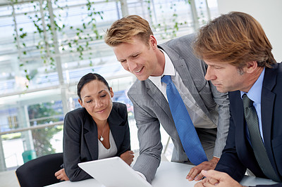 Buy stock photo A young businessman showing his colleagues something on a digital tablet