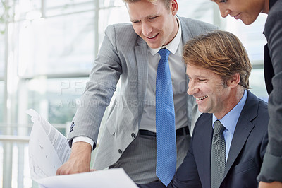 Buy stock photo A group of architects reviewing building plans in their office