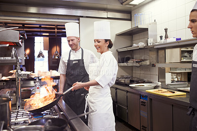 Buy stock photo Shot of chefs flambeing in a restaurant kitchen
