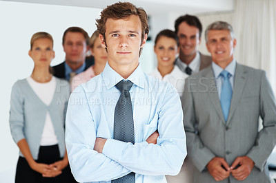 Buy stock photo Smart young businessman standing confidently with his colleagues in background