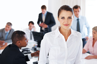 Buy stock photo Portrait of a confident young businesswoman at the meeting with colleagues working behind