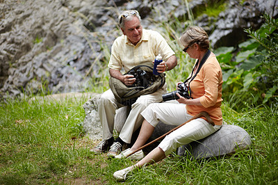 Buy stock photo A loving senior couple stopping for a water break while out for a walk in nature