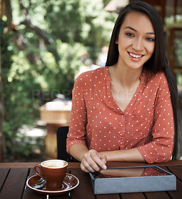 Buy stock photo Shot of a young woman using a digital tablet at a cafe