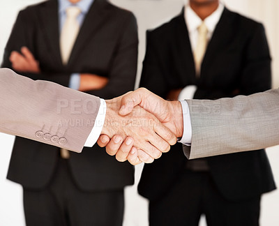 Buy stock photo Closeup of hand shake of two business partners closing a buisiness deal with colleagues at back