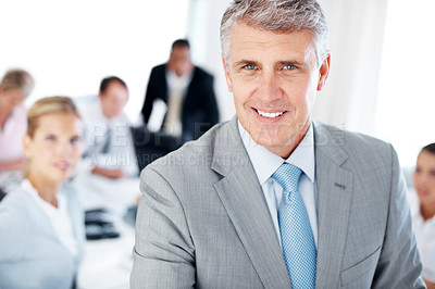Buy stock photo Closeup portrait of a smiling mature businessman and his team working in background