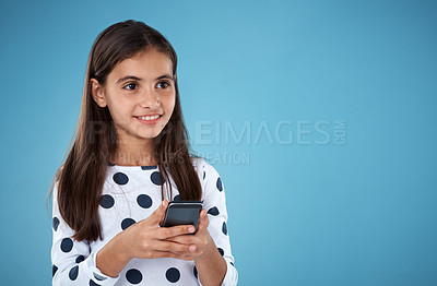 Buy stock photo Studio shot of a little girl sending a text message on her cellphone