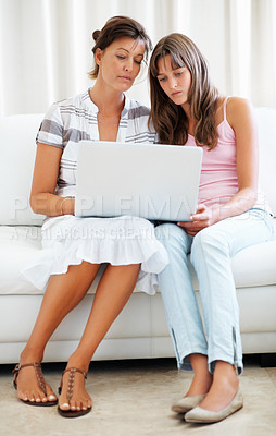 Buy stock photo Full length of mother and daughter sitting on a sofa and browsing internet using laptop