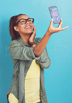 Buy stock photo Shot of a young woman taking a selfie against a blue background