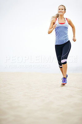 Buy stock photo Shot of a young woman jogging on the beach