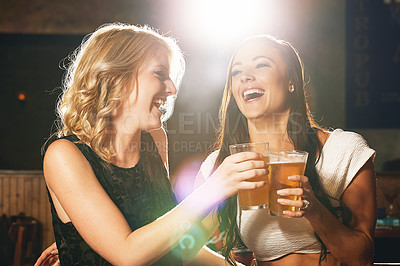Buy stock photo Shot of two young women enjoying a beer together in a nightclub