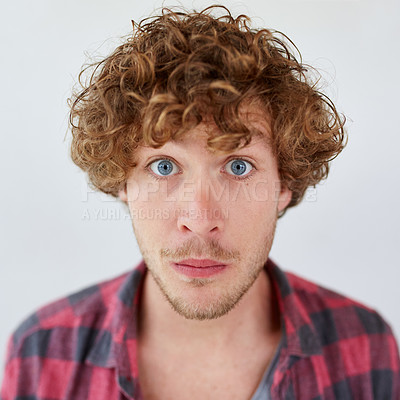 Buy stock photo Studio portrait of a young man looking surprised against a gray background
