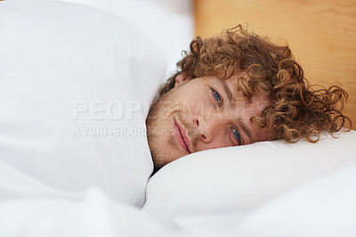 Buy stock photo Cropped portrait of a young man lying in his bed