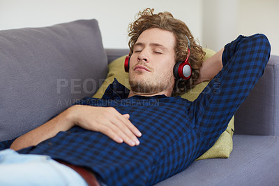 Buy stock photo Shot of a young man lying on a sofa listening to music on headphones