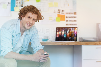 Buy stock photo Portrait of a young designer using his cellphone while working in his home office