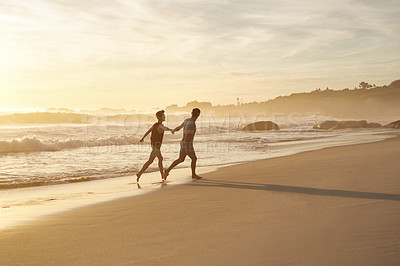 Buy stock photo Shot of a young couple having fun at the beach