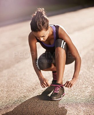 Buy stock photo Shot of a runner tying her shoelaces before a run