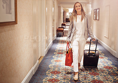 Buy stock photo Shot of a woman walking down the corridor of a hotel with a suitcase