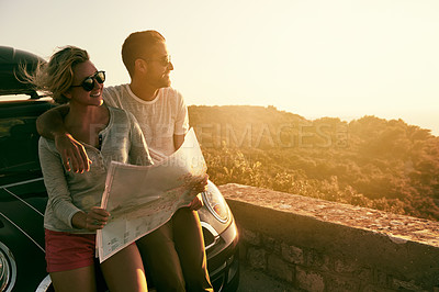 Buy stock photo Shot of a couple reading a map on their road trip