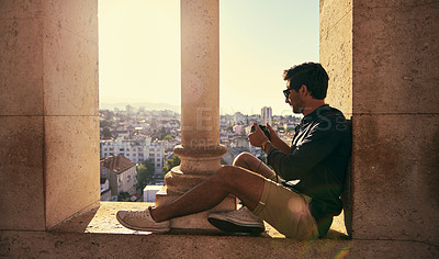 Buy stock photo Shot of a young tourist taking pictures while touring a foreign city