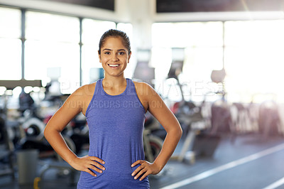 Buy stock photo Cropped portrait of a young woman standing with her hands on her hips in the gym