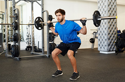 Buy stock photo Full length shot of a young man lifting a barbell in the gym