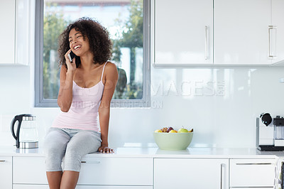 Buy stock photo Shot of a young woman talking on a cellphone while sitting on her kitchen counter
