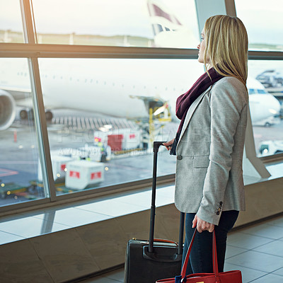 Buy stock photo Shot of a young woman standing in an airport looking out the window