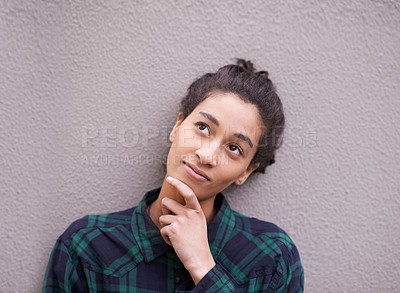 Buy stock photo Shot of a young woman looking thoughtful while standing outside