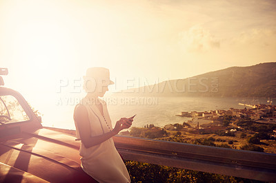 Buy stock photo Shot of a woman using her cellphone while taking a break from her road trip